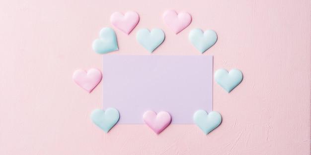 Lila pastellkarte und herzen auf rosa fahne