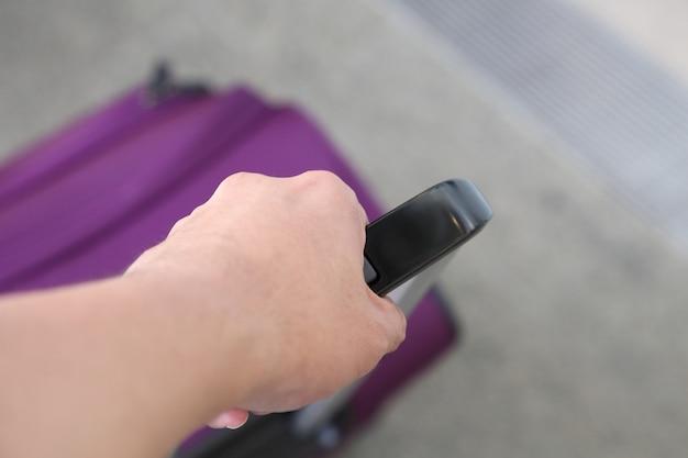 Lila reisekoffer am flughafen halten