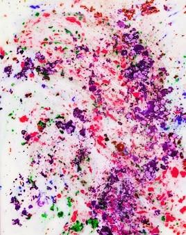 Lila; rosafarbenes und grünes holi farbpulver gemischt auf weißem hintergrund