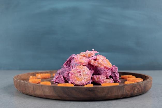 Lila rote-bete-karotten-salat auf einem holzbrett.