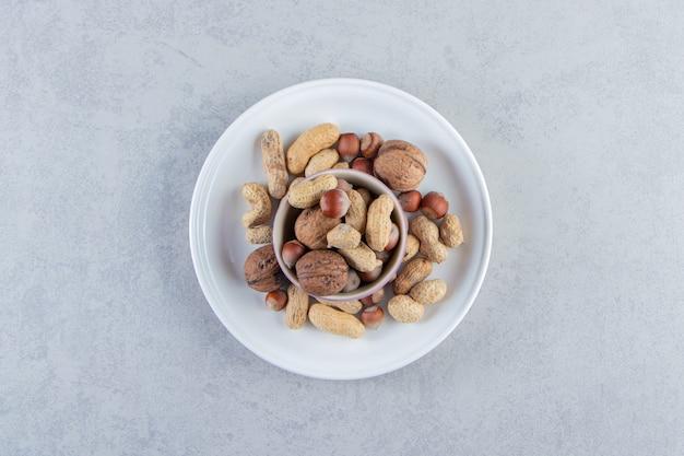Lila schüssel voller verschiedener geschälter nüsse auf steinhintergrund.