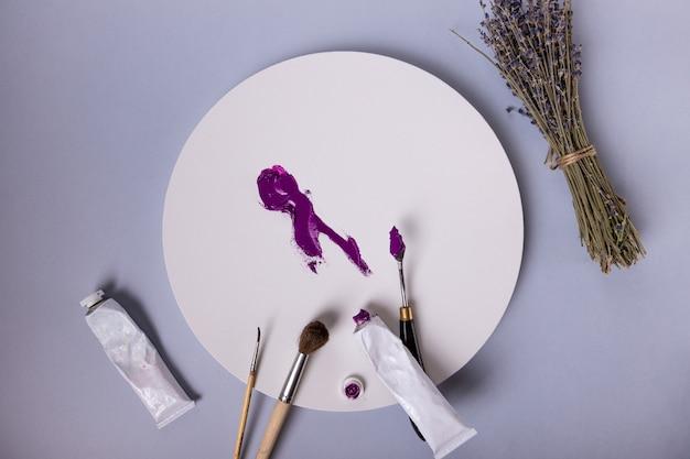 Lila striche auf einer runden leinwand pinsel mastikhin-farben und ein haufen lavendel schönes layout o ...
