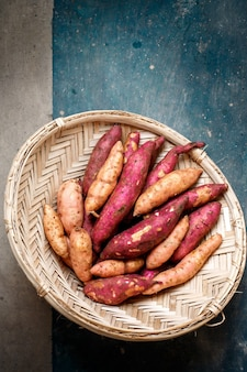 Lila süßkartoffel in einem metallsieb auf dunklem hintergrund