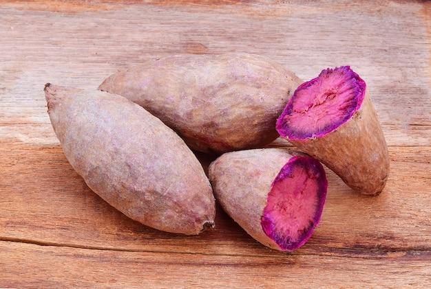 Lila süßkartoffeln auf einem holztisch
