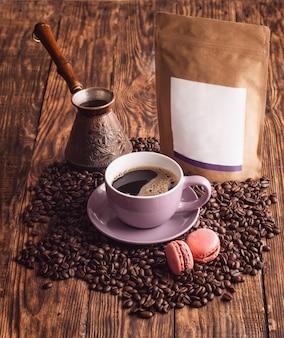 Lila tasse kaffee, makronen, bohnen, türkische kaffeekanne und bastelpapierbeutel auf hölzernem hintergrund