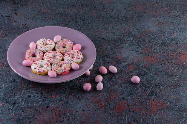 Lila teller mit bunten leckeren donuts auf dunkler oberfläche.