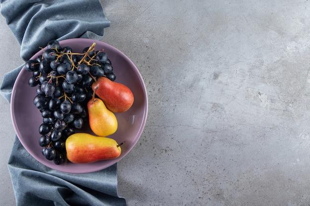 Lila teller mit frischen schwarzen trauben und birnen auf steinoberfläche