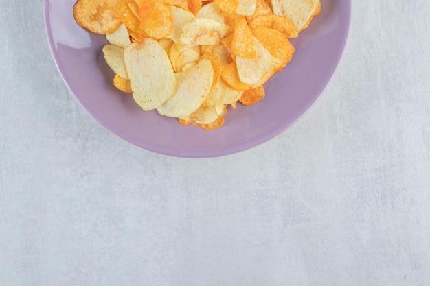 Lila teller mit verschiedenen knusprigen chips auf stein.