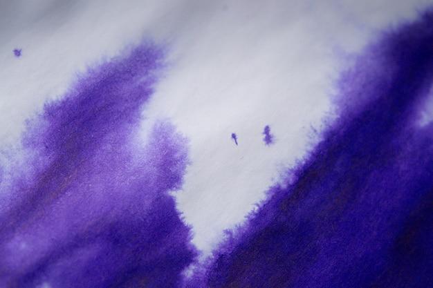 Lila tintenfleck auf einem blatt weißes papiermakro. abstrakter hintergrund. verteilt tintenflecken mit streifen auf weißem hintergrund