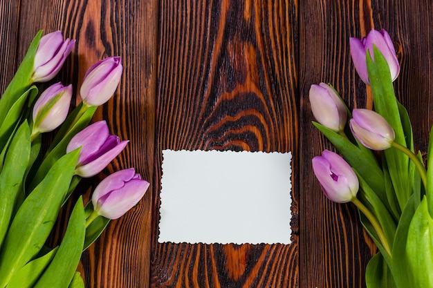 Lila tulpen auf einem dunklen hölzernen hintergrund und einer weißen grußkarte