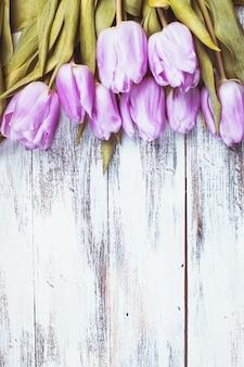 Lila tulpen über schäbigen weißen holztisch