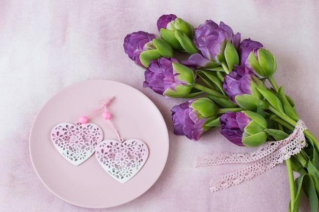 Lila tulpen und zwei herzen in einem rosa teller