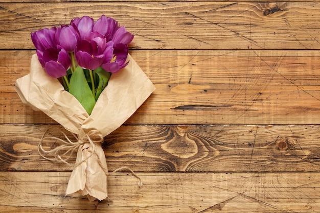 Lila tulpenstrauß auf holztischoberansicht