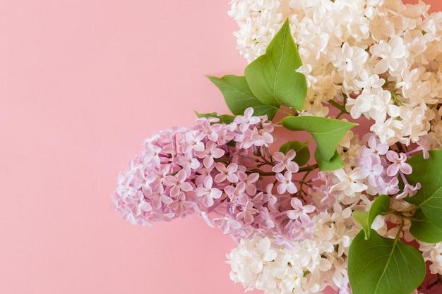 Lila und weißer fliederstrauß auf rosa hintergrund. blumengesteck
