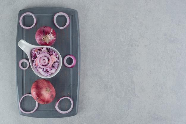 Lila zwiebelsalat in einer keramiktasse auf betonoberfläche