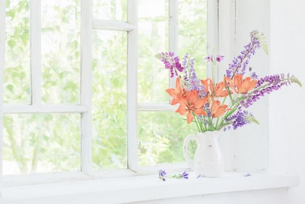 Lilien- und lupinenblüten im krug auf der fensterbank