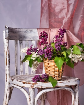 Lillac blumenstrauß in der vase auf vintage holzstuhl