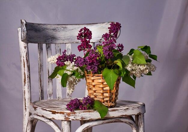 Lillac bouquet in vase auf vintage holzstuhl