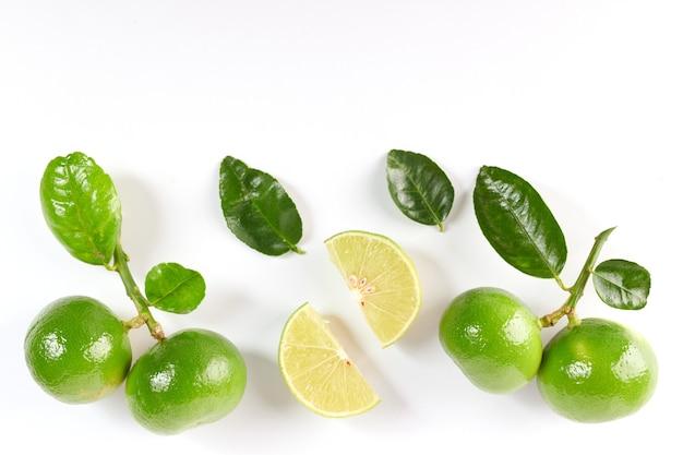 Limette mit hälfte und blatt auf weißer oberfläche isoliert. frisches obst mit blatt. set oder sammlung. flach liegen. es ist frisch aus heimischem bio-garten gepflückt. lebensmittelkonzept.