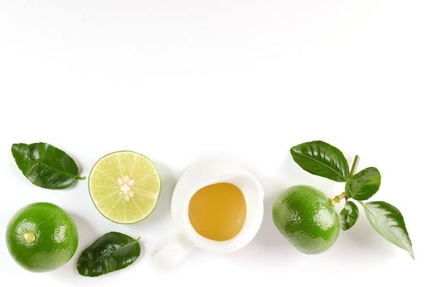 Limette mit hälfte und blatt auf weißer oberfläche isoliert. frisches obst mit blatt. set oder sammlung. zitronensaft und grüne zitrone. flach liegen. es ist frisch gepflückt aus heimischem bio-garten. lebensmittelkonzept