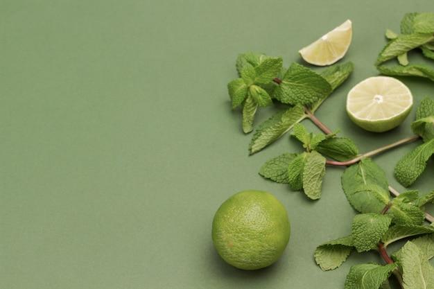 Limette und minze auf grüner oberfläche