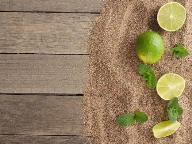 Limette und pfefferminze auf dem sand draufsicht kopienraum sommerferienkonzept