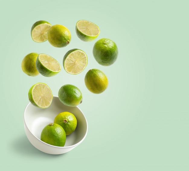 Limetten fliegen in der weißen schüssel auf grünem hintergrund