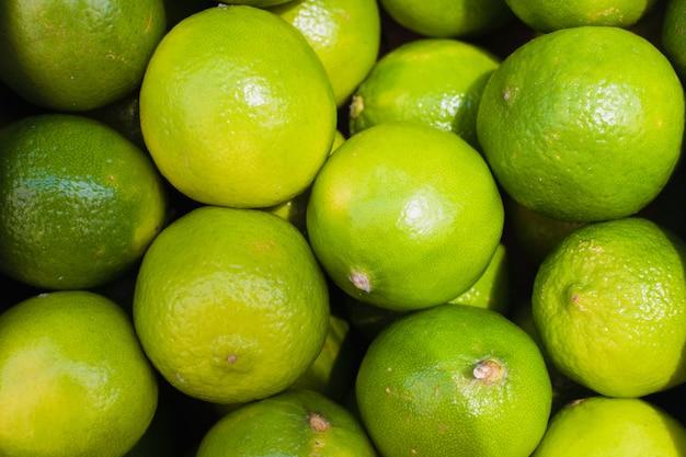 Limetten in einer box auf dem markt. grüner kalkmusterhintergrund