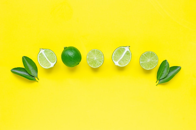 Limetten mit blättern auf gelbem grund.