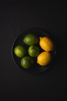Limetten- und zitronensauerfrüchte in schwarzer platte auf stimmungsvoller dunkelheit
