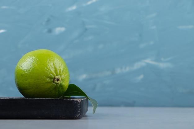 Limettenfrucht mit blättern auf schneidebrett.
