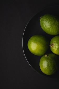 Limettensauerfrüchte in der schwarzen platte auf stimmungsvoller dunkelheit