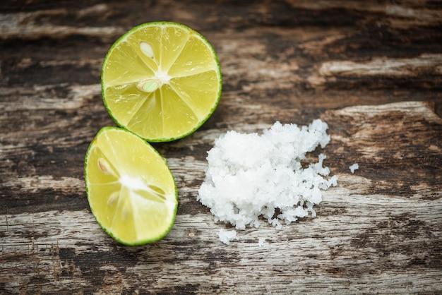 Limettenscheibe und salz auf rustikalem holz