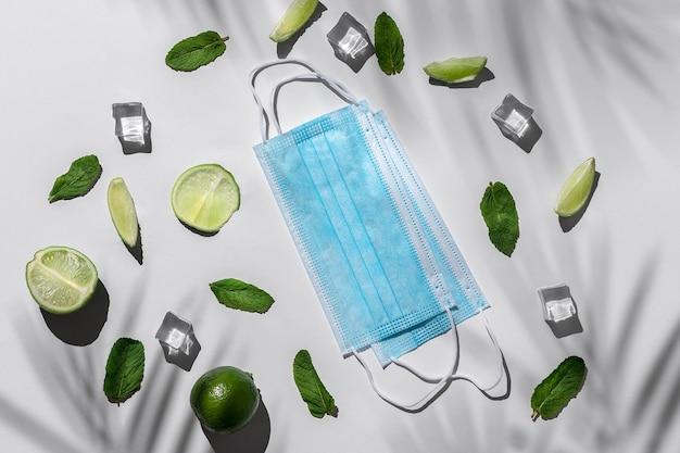 Limettenstücke, grüne minze und eiswürfel, reisekonzept mit medizinischen masken