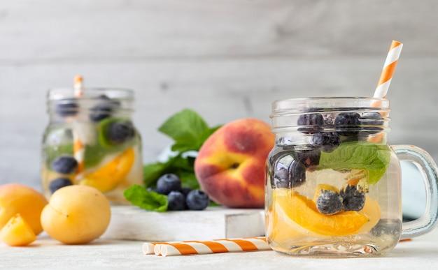 Limonade aus aprikosen, heidelbeeren und frischer minze in gläsern.