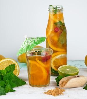 Limonade des sommerauffrischungsgetränks mit zitronen, moosbeere, tadellosen blättern und kalk in einer glasflasche