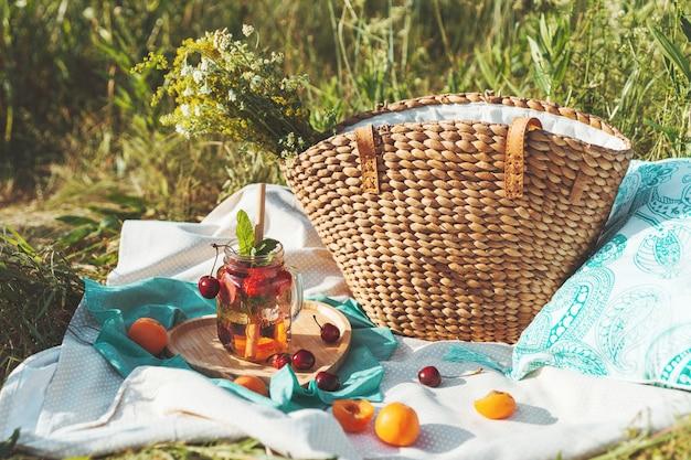 Limonade in einem glasbecher und mit einem bambusstroh, ein umweltfreundliches sommerpicknick.