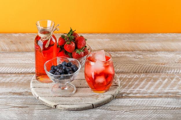 Limonade in krug und glas mit erdbeeren, blaubeeren, schneidebrett hohe winkelansicht auf orange und holzoberfläche