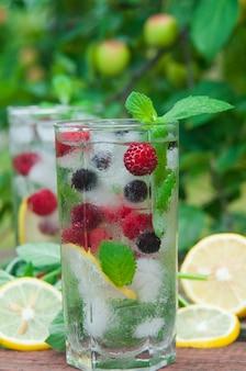 Limonade mit beeren, minze und eiswürfeln in einem glas