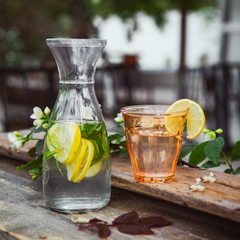 Limonade mit blumen auf zweig in glas und krug auf holz und hof tisch, seitenansicht.