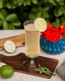 Limonade mit eiswürfeln und limettenscheibe.