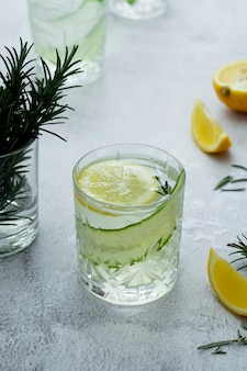 Limonade mit frischen gurken, zitronen und rosmarin in einem glas auf hellem hintergrund Premium Fotos
