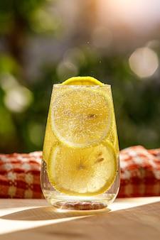 Limonade mit frischer zitrone im glas auf garde auf unscharfem garten