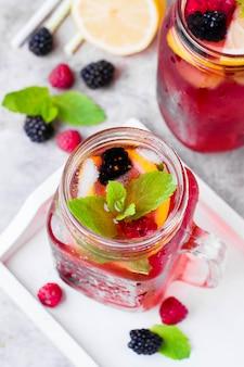 Limonade mit himbeere und brombeere mit zitrone, minze im einmachglas.