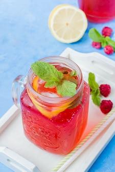Limonade mit himbeere und brombeere mit zitrone, minze im weckglas auf tabelle