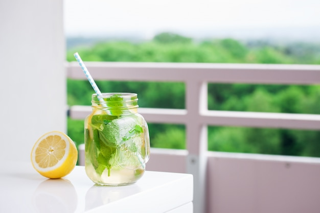 Limonade mit strohhalm neben einer zitrone