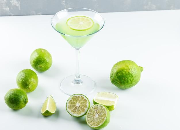 Limonade mit zitrone in einem glas auf weiß und gips, hohe winkelansicht.
