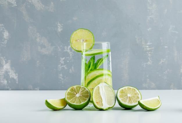 Limonade mit zitronen, kräutern in einem glas auf weiß und gips,