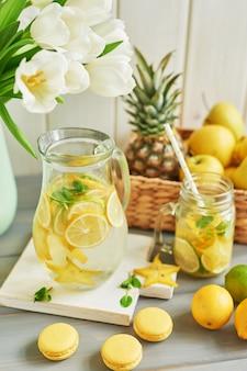 Limonade, süße macarons, früchte und tulpenblüten