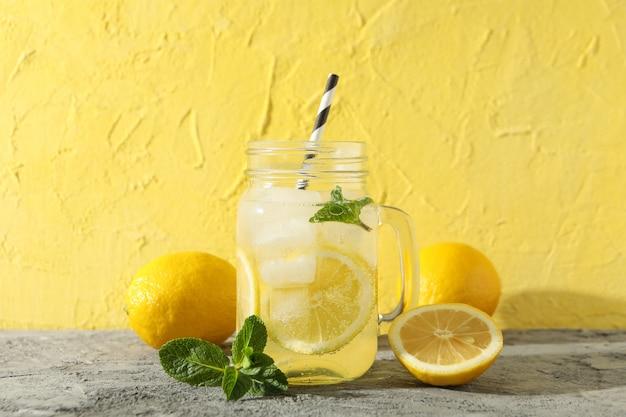Limonade, zitronen und minze auf grauem tisch. frisches getränk